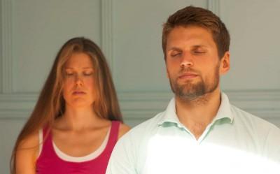 Homme et femme assis avec les yeux fermés pendant un cours de méditation.