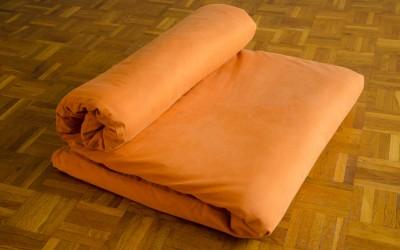 Tapis de yoga futon avec housse en orange en mode méditation.
