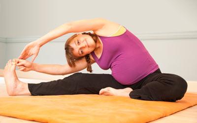 Posture de yoga prénatal durant un cours pour les femmes enceintes.